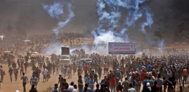 14.mai.2018 - Palestinos correm de bombas de gás durante protesto na fronteira da Faixa de Gaza com Israel - Mohammed Abed/AFP