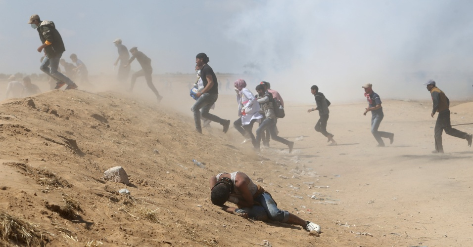 15.mai.2018 - Palestinos correm de bombas de gás lacrimogênio durante confronto com forças israelenses na Faixa de Gaza