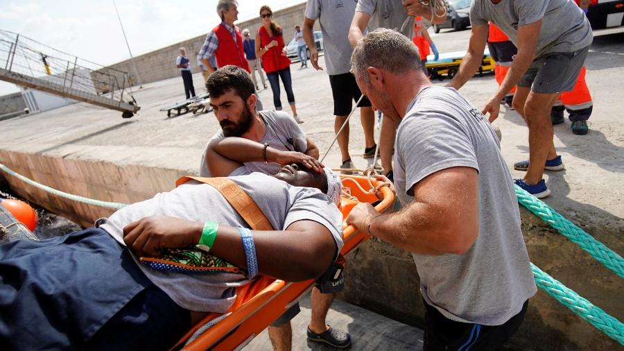Equipe da ONG Proactiva Open Arms carrega Josefa, a mulher resgatada na última terça-feira, após naufrágio no mar Mediterrâneo - Juan Medina / REUTERS
