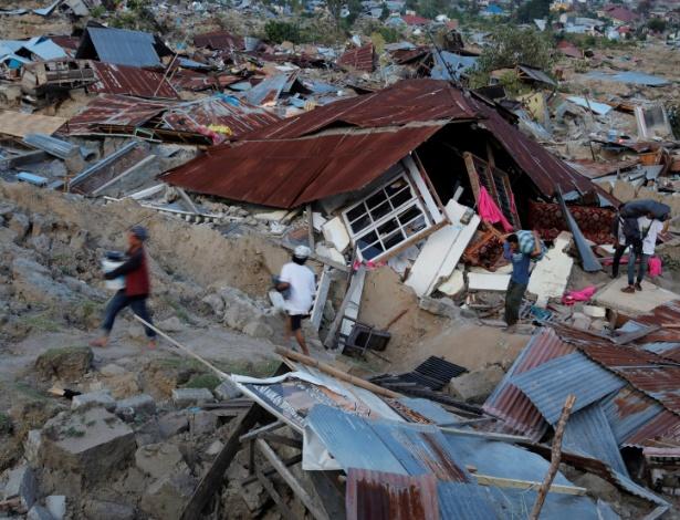 1.out.2018 - Sobreviventes tentam recuperar o possível em meio à destruição deixada em Palu, na Indonésia