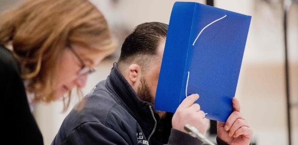 Niels Högel esconde o rosto durante julgamento na Alemanha, nesta terça (30) - Julian Stratenschulte/AFP