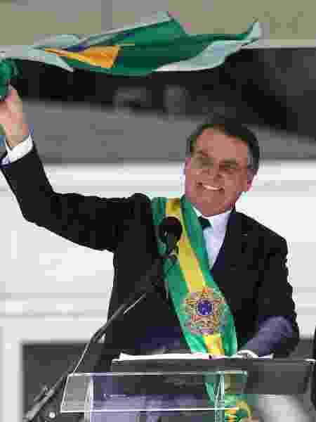Jair Bolsonaro exibe a bandeira do Brasil após discursar no Palácio do Planalto - Wilton Junior/Estadão COnteúdo