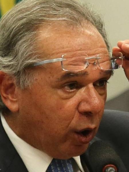 Paulo Guedes retira os óculos para fixar o olhar num ponto distante - Foto: Jorge William/Agência O Globo