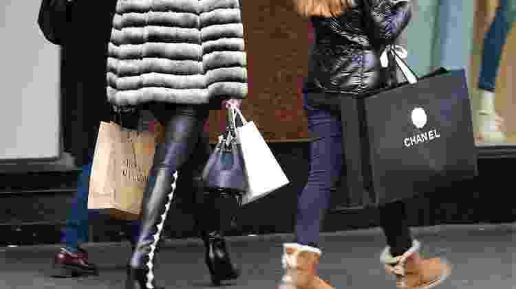 Consumidores com sacolas de compra do lado de fora de loja de departamento em Paris - Charles Platiau - Charles Platiau