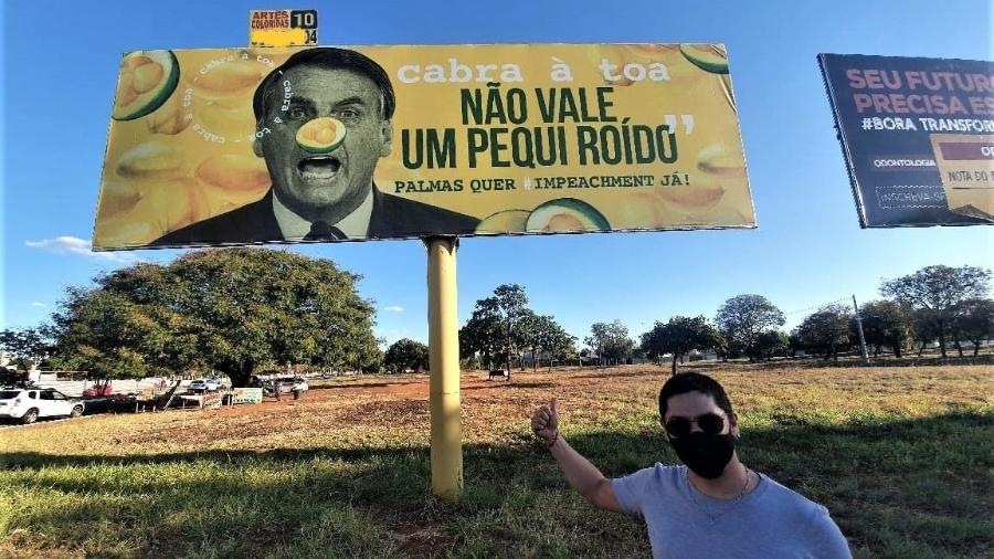 O sociólogo Tiago Costa Rodrigues aponta para outdoor instalado em agosto de 2020 em Palmas (TO) - Edy Passos/Álbum de família