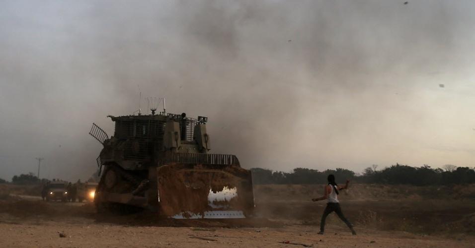 14.out.2015 - Palestino joga pedra contra escavadeira militar israelense em Bureij, na faixa de Gaza. A escalada de violência entre palestinos e israelenses tem crescido na região, o que aumenta os temores de uma terceira Intifada, o levante palestino