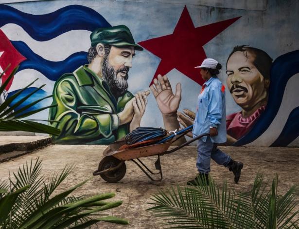 Trabalhadora passa por mural que retrata o líder cubano Fidel Castro (à esquerda) e o presidente da Nicarágua, Daniel Ortega, em Manágua (capital do país)