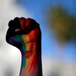 Manifestante levanta braço com punho cerrado e colorido com cores da causa LGBT em vigília em Los Angeles, na Califórnia, pelas vítimas de atentado em boate gay em Orlando (EUA)