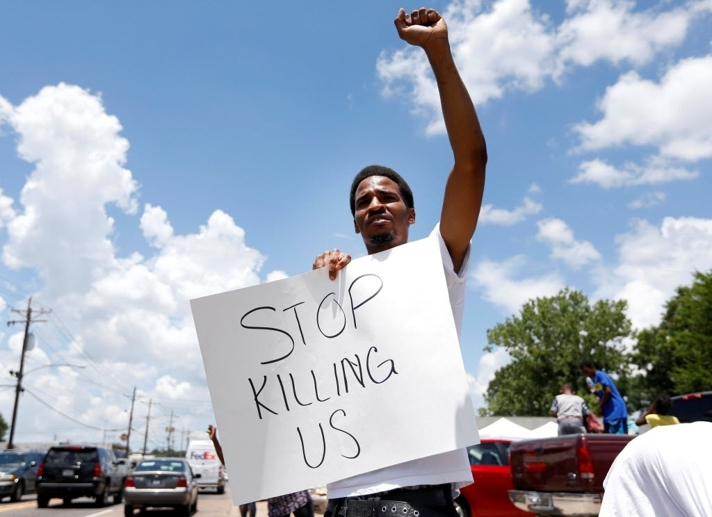 """7.jul.2016 - O manifestante Lakeith Howard segura uma placa com os dizeres: """"Parem de nos matar"""" (em tradução do inglês), durante protesto contra a morte de negros por policiais em Baton Rouge, Louisiana, nos Estados Unidos. O local virou palco de manifestações após um vídeo amador mostrar o momento em que Alton Sterling, um homem negro de 37 anos, foi assassinado por policiais mesmo estando rendido"""