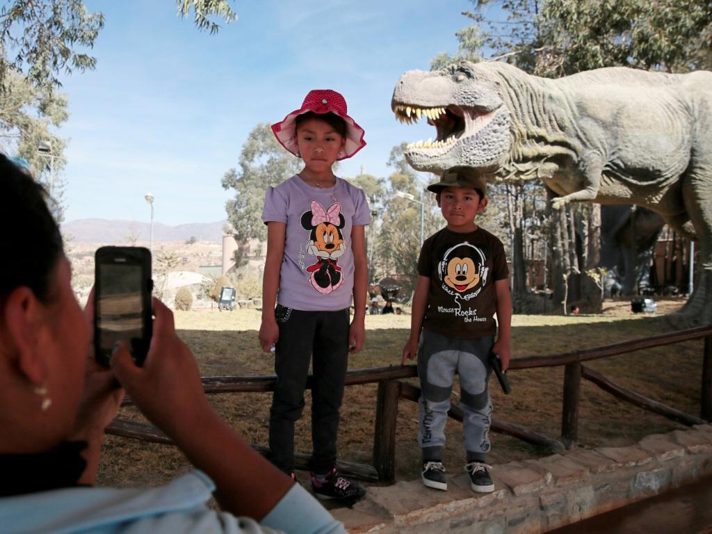 17.ago.2016 - Mãe tira foto de seus filhos ao visitar o Jurassic Park da vida real, também conhecido como parque Cretaceous, em Cal Orcko, na Bolívia. O parque cheio de dinossauros de brinquedo fica próximo ao local onde arqueólogos descobriram uma pegada de cerca de 1,20 metros de diâmetro que pertenceu à um dinossauro que viveu há 80 milhões de anos