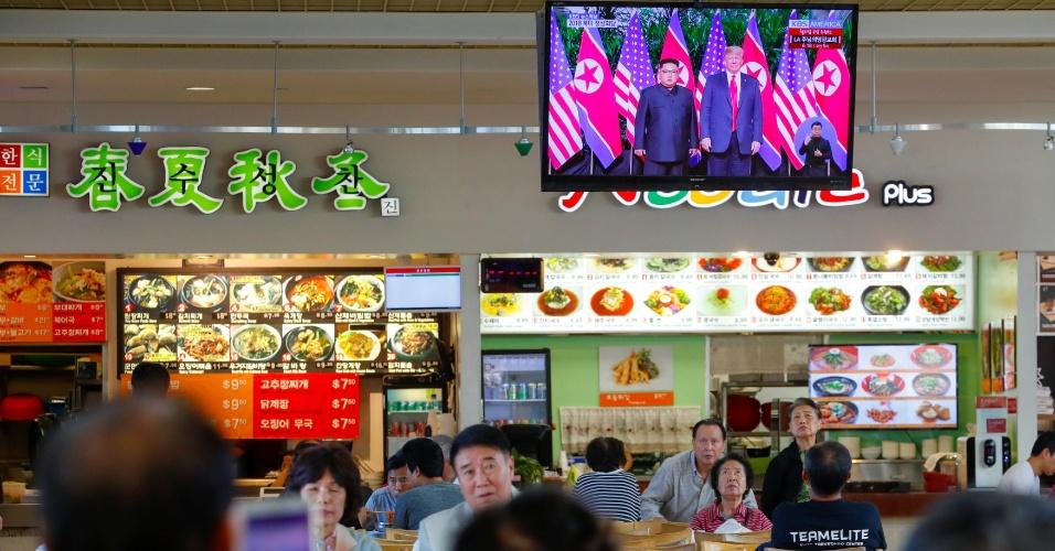 11.jun.2018 - As pessoas assistem de uma praça de alimentação em Los Angeles, nos Estados Unidos, o histórico aperto de mão do presidente dos EUA, Donald Trump, e do líder norte-coreano,  Kim Jong-un