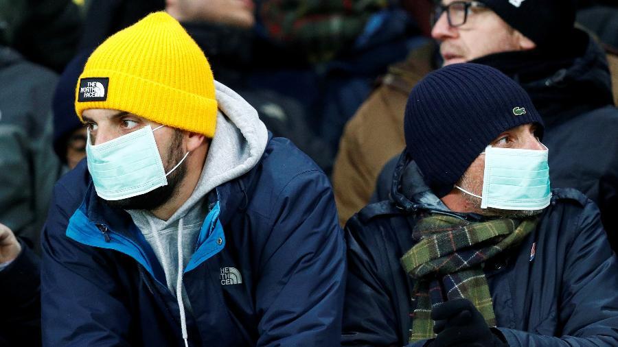 Torcedores da Roma utilizam máscara de proteção contra coronavírus em partida contra Gent pela Liga Europa - FRANCOIS LENOIR