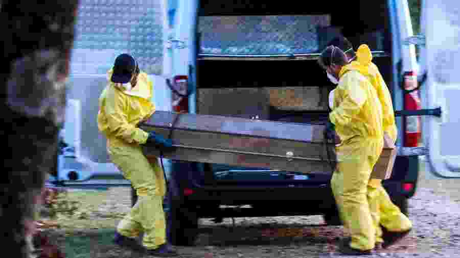 Homens carregam corpo de paciente morta por covid-19 no Cemitério Santo Antônio, em Sorocaba (SP) - Cadu Rolim - 6.abr.2020/Fotoarena/Estadão Conteúdo