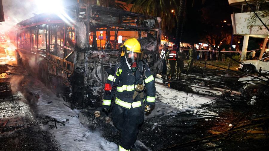 A equipede emergência israelense trabalha ao redor de um ônibus depois que foguetes são lançados contra Israel - Ahmad Gharabli/AFP