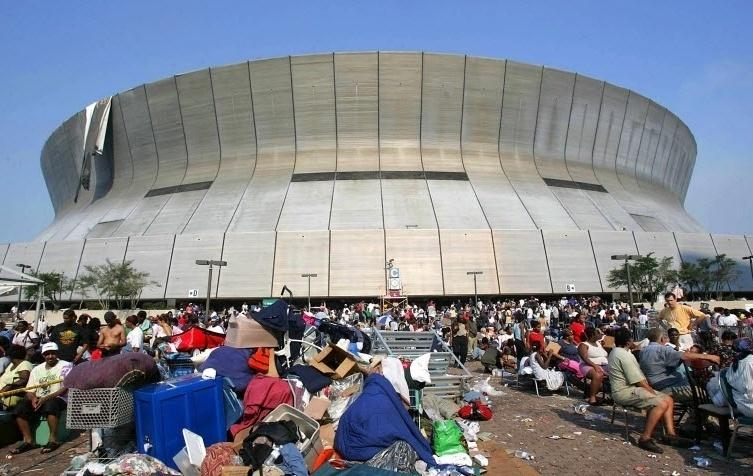 2005: Desalojados sentam em frente ao estádio Superdome, em Nova Orleans, Louisiana (EUA), no rescaldo do furacão Katrina, que varreu edifícios, alagou quase totalmente a cidade e causou mais de 1.800 mortes