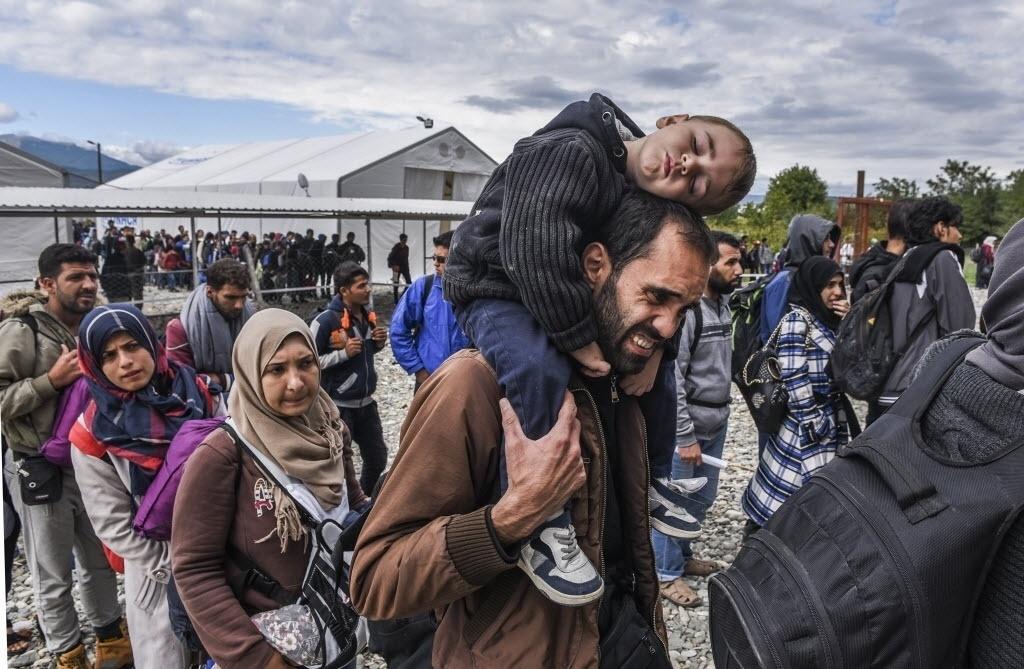 28.set.2015 - Migrantes fazem fila enquanto aguardam para pegar um trem no campo de registro, que fica na fronteira entre Macedônia e Grécia