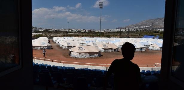 Jovem refugiado caminha diante das tendas no campo de refugiados Helliniko