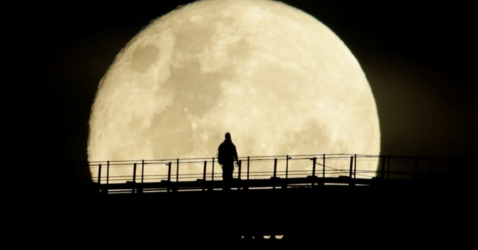Homem atravessa ponte em Sydney, Austrália, sob o luar da superlua