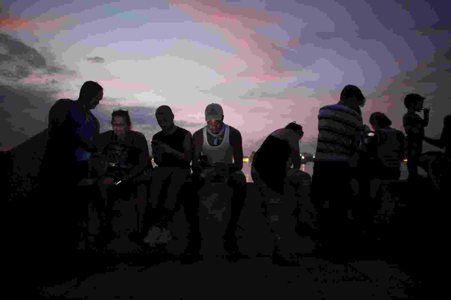 Pessoas se conectam à internet por meio de um ponto de Wi-Fi instalado pelo governo cubano, em Regla - Alexandre Meneghini/Reuters