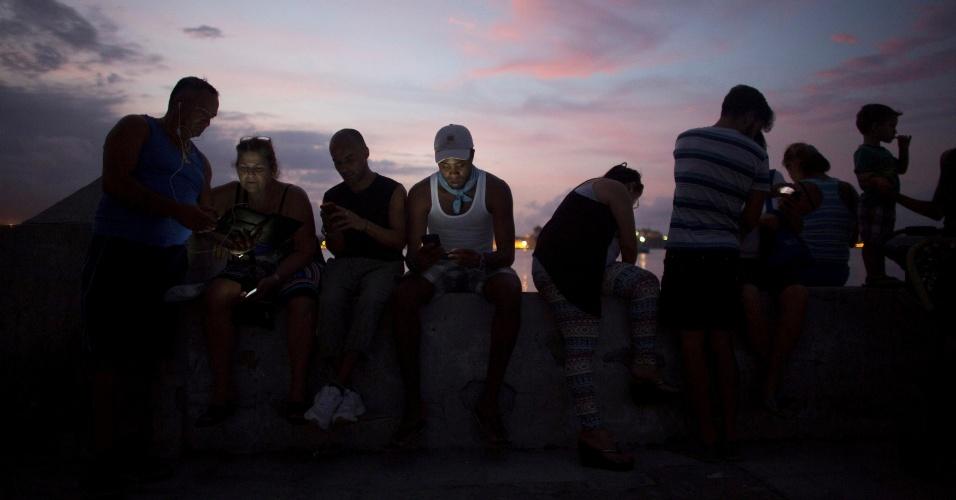 Pessoas se conectam à internet por meio de um ponto de Wi-Fi instalado pelo governo cubano, em Regla