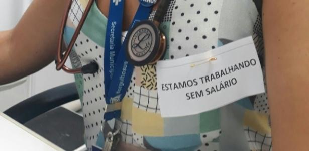 Funcionários de saúde usam bilhete na roupa denunciando salários em atraso