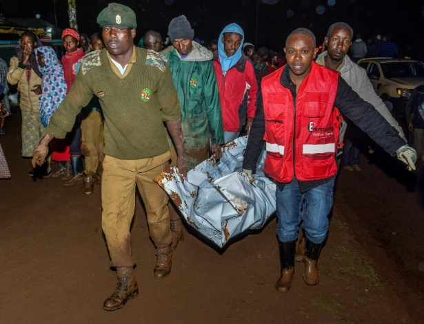 Homens carregam corpo de vítima do rompimento de represa em Solai, no Quênia