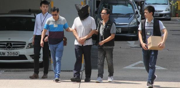 Malaio Khaw Kim-sun é escoltado pela polícia em setembro de 2017 em Hong Kong após ser acusado de matar a mulher e a filha - AFP