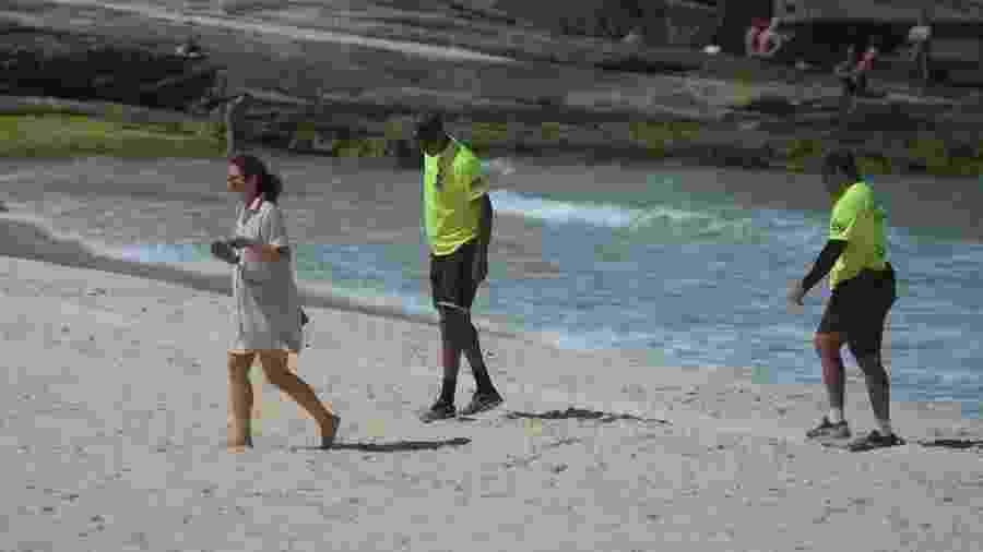 Policiais militares abordam mulher que desrespeitou bloqueio em praia na zona sul do Rio - ERBS JR./FRAMEPHOTO/ ESTADÃO CONTEÚDO