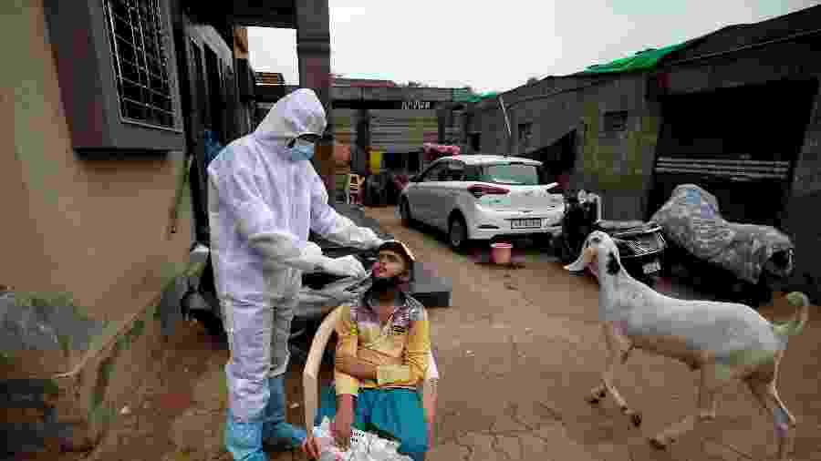 24.jul.2020 - Profissional da saúde usando roupa protetora faz teste em garoto em meio à pandemia do novo coronavírus em Ahmedabad, na Índia - Amit Dave/Reuters