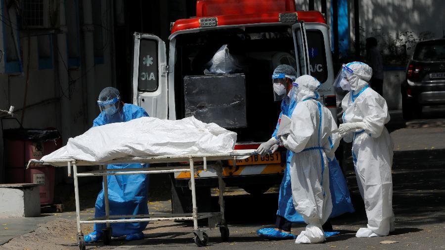 Profissionais de um necrotério colocam corpo de pessoa que morreu de covid-19 em ambulância em Nova Délhi para transportá-lo para cremação - Por Tanvi Mehta