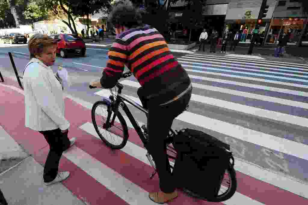 29.jun.2015 - Pedestre distraída para no meio da ciclovia e atrapalha passagem de ciclista. A ciclovia da avenida Paulista teve seu primeiro dia útil nesta segunda-feira. Há ilhas para pedestres no meio da avenida. - Júnior Lago/UOL