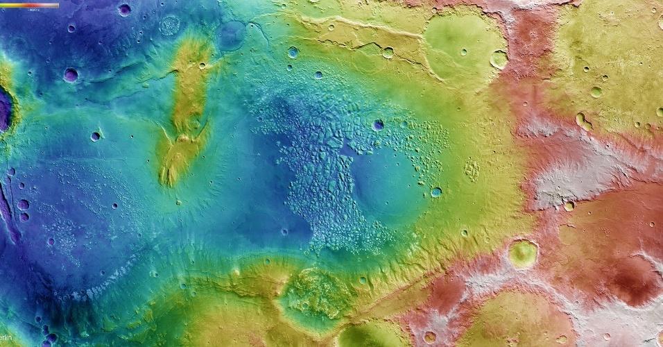 3.ago.2015 - Esta imagem colorida é um mapa da topografia de uma região conhecida como Terra Sirenum, localizada no hemisfério sul de Marte. A cor vermelha e branca representa uma topografia mais alta, e as áreas azul e roxa, mais baixa. A imagem é de uma área imensa onde há falésias, crateras de impacto, canais esculpidos em encostas íngremes, cumes enrugados e escarpas, que juntos refletem uma história geológica rica. Talvez o aspecto mais importante é a porção de terreno irregular em direção ao centro da imagem. Esta é a Atlantis Caos, uma planície que se estende por mais de 200 km, que contém algumas centenas de pequenos picos e morros de topo achatado. Acredita-se que o local foi alvo de uma erosão lenta. Os cientistas suspeitam que algumas das crateras e bacias podem abrigar água parada, já que os canais esculpidas nas encostas fornecem evidências de que já houve água nesta região