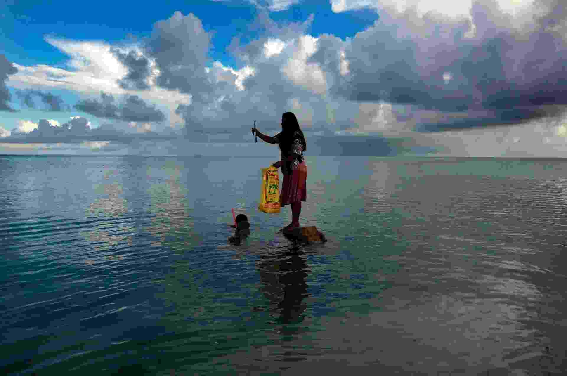 25.mai.2013 - Casal pesca no arquipélago de Kiribati, na Oceania, um dos mais vulneráveis ao aumento no nível dos oceanos - David Gray/Reuters