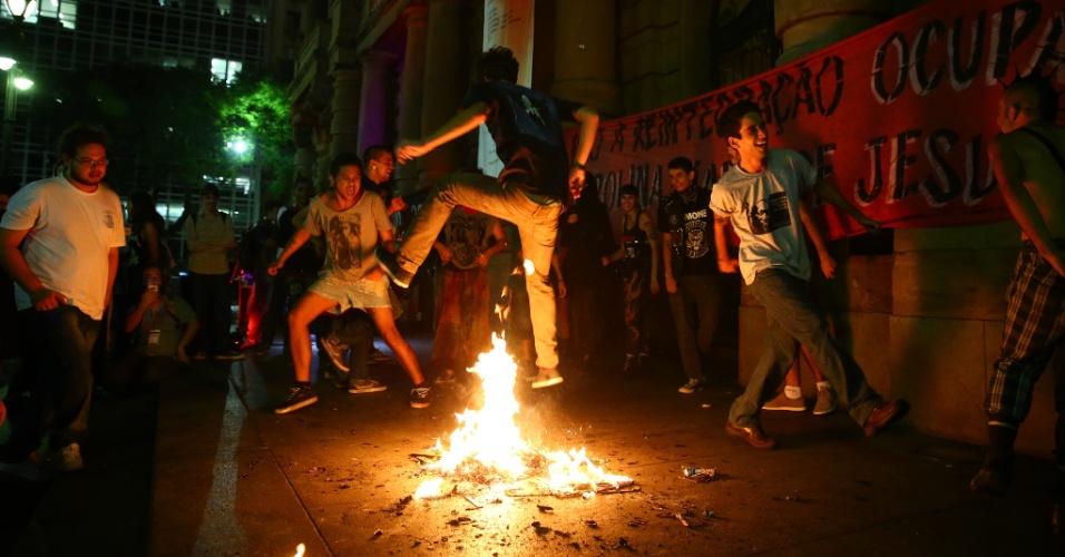 25.fev.2016 - Manifestantes pulam catraca incendiada durante novo protesto do Movimento Passe Livre (MPL) contra o aumento das tarifas do transporte público em São Paulo (SP). Grupo se reuniu no Teatro Municipal, no centro paulistano. Evento contou com shows, debates e forte presença da polícia