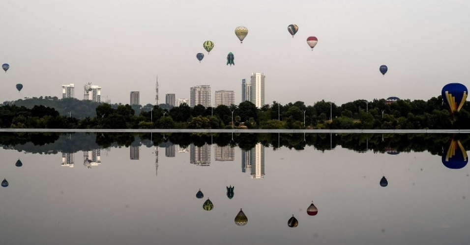11.mar.2016 - Balões participantes do International Hot Air Balloon Fiesta são refletidos em lago ao voarem por Putrajaya, na Malásia. O evento teve início nesta sexta-feira (11) e termina no domingo (13). Nesta edição, foram inscritos balões de 13 países
