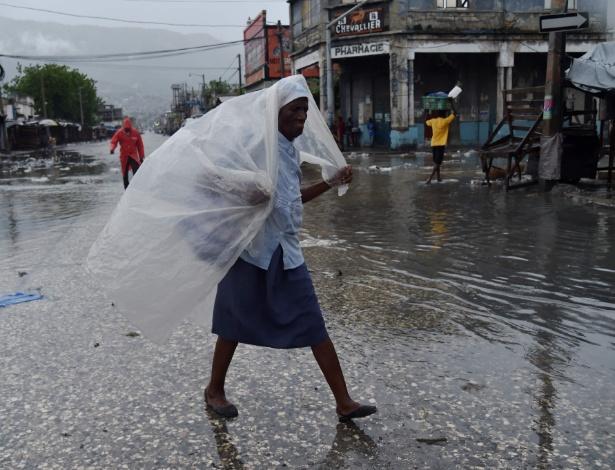 Mulher se protege da chuva com pedaço de plástico após a chegada do furacão Matthew em Porto Príncipe, no Haiti
