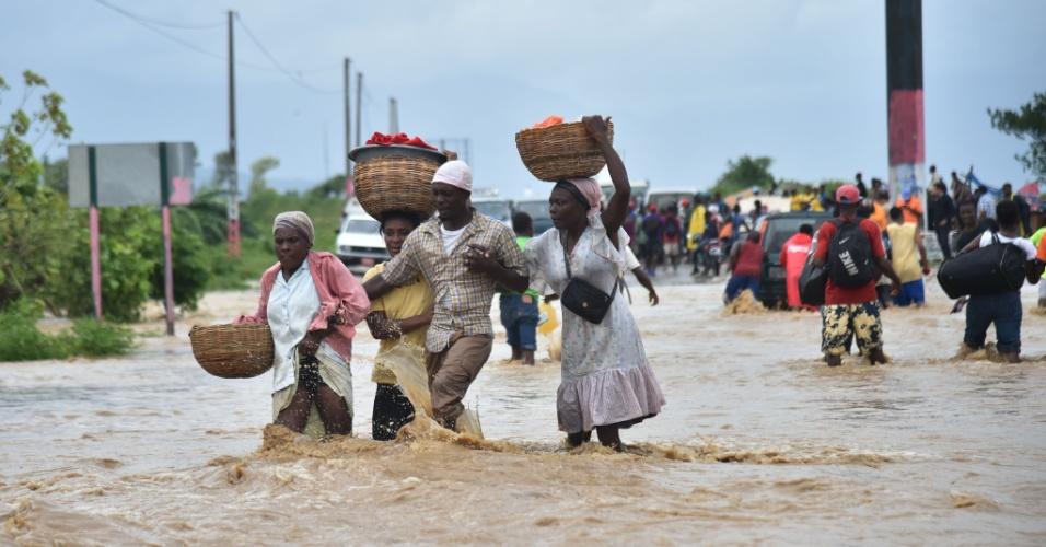 5.out.2016 - Pessoas tentam atravessar estrada inundada pela cheia do rio Rouyonne na comuna de Leogane, em Porto Príncipe, capital do Haiti