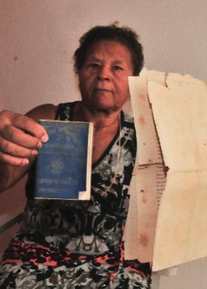Nilza Ferreira da Silva segura os únicos documentos que salvou após a inundação