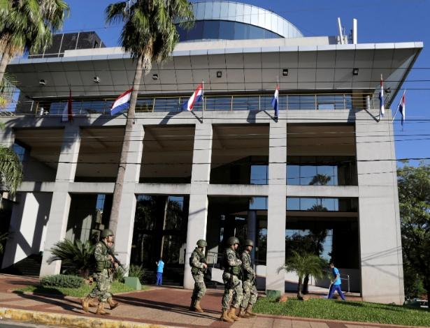 Soldados caminham diante do Congresso paraguaio enquanto parlamentares discutem mudança na lei da reeleição, em Assunção