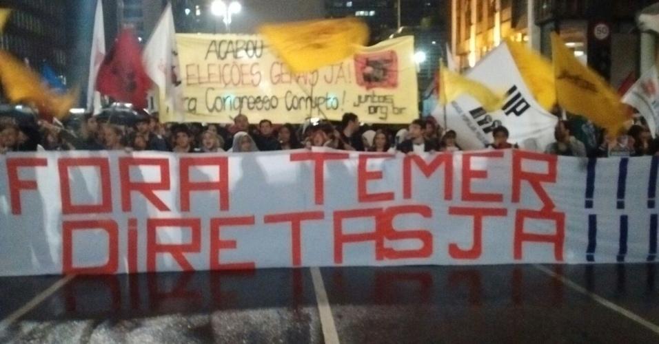 """18.mai.2017 - Com bandeiras e sob chuva, manifestantes protestam em São Paulo com faixa de """"Fora Temer, Diretas Já!"""""""