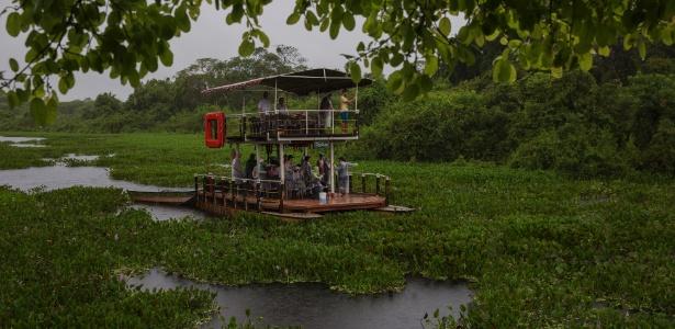 Barco com turistas navega em região alagada do Pantanal, em Miranda