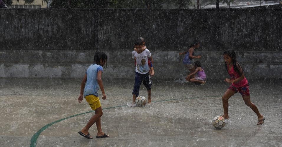 9.maio.2018 - Sob chuva, crianças jogam futebol na região metropolitana de Manila, nas Filipinas