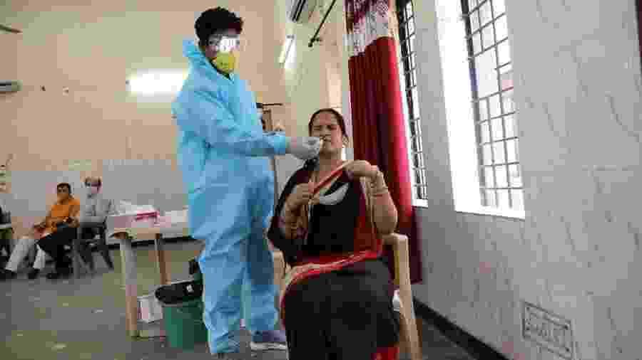 Profissional médico coleta amostra com swab para exame de detecção do coronavírus em Noida, na Índia - EFE/EPA/HARISH TYAGI