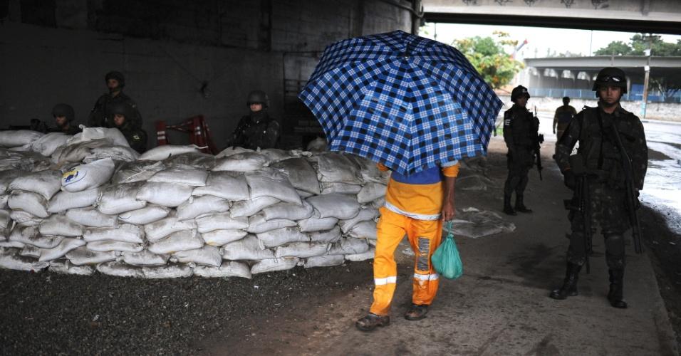 19.jun.2015 - Morador passa por barricada das Forças Armadas na entrada da comunidade Vila dos Pinheiros, no complexo da Maré, zona norte do Rio de Janeiro. A Força de Pacificação vai deixar as favelas no dia 30 de junho, após 15 meses de ocupação