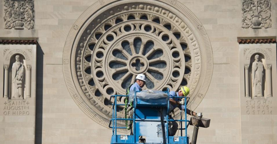 17.set.2015 - Trabalhadores removem um poste de luz de frente da Basílica do Santuário Nacional de Imaculada Conceição que abrigará uma missa a ser celebrada pelo papa Francisco, em Washington (EUA). O pontífice começará no próximo sábado (19) sua 10ª viagem internacional, um périplo que o levará a