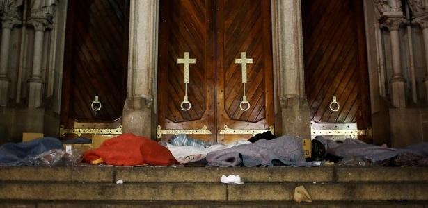 Moradores de rua se protegem do frio intenso nas escadarias da catedral da Sé