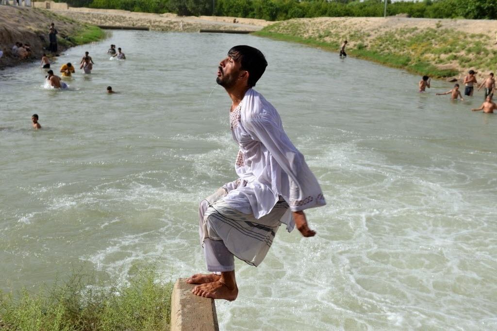 23.jun.2016 - Homem salta para nadar em canal em Candaar, no Afeganistão, durante o Ramadã, o mês sagrado para os mulçumanos. O período especial é usado para o aprofundamento da fé
