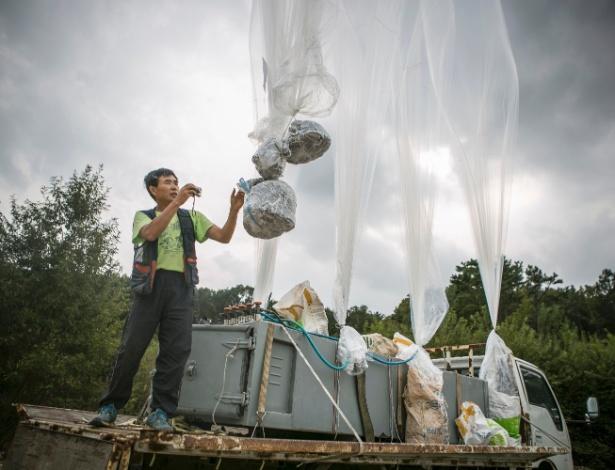 Lee Min-bok fotografa seus balões enquanto os solta, na fronteira com a Coreia do Norte