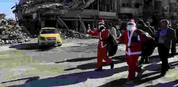 Homens vestidos de Papai Noel caminham pelas ruínas da cidade de Raqqa, na Síria - Delil Souleiman/AFP - Delil Souleiman/AFP
