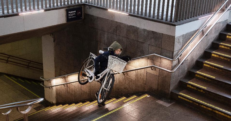 a636ffffb48d5 Moradora de Copenhague carrega sua bicicleta em escadaria de estação de  metrô